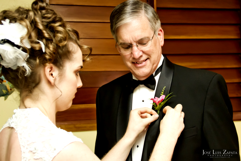 Bride putting boutonniere on dad.